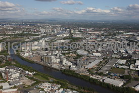 Manchester aerial photograph of a wide angle view of a Industrial  landscape looking across the Manchester Ship Canal on the north side of Trafford Park Estate with Media City and Salford Quays with Manchester United Football Stadium and the hills in the distance