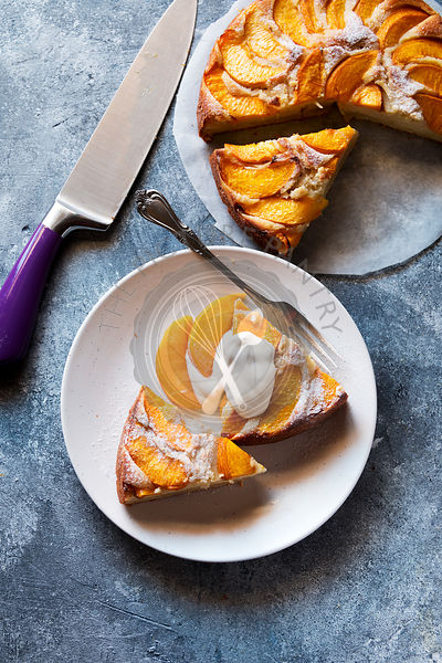 Two slices of peach cake on a plate served with yogurt.Top view