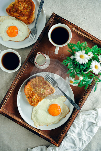 Easy French toast served with a fried egg on the side on a white plate, a cup of coffee, milk and spring flowers in a wooden tray photographed from top view. Another plate with a french toast and an egg and another coffee cup accompany.