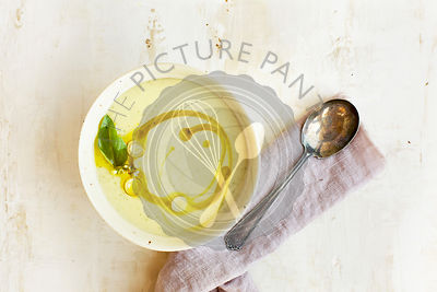 Coconut Basil White Bean Bisque with Lemongrass Oil.  Photographed on a rustic white background.