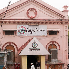 A man orders coffee from a waiter  as he enters the Indian Coffee House, Allahabad