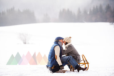 Happy senior couple sitting face to face on sledge in winter landscape