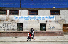 Family walking past Association of Retired Railway Workers building, Uyuni, Bolivia