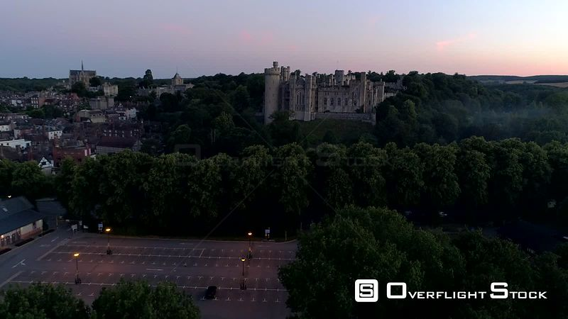 Drone rises to reveal Arundel Castle and town in the twilight before dawn