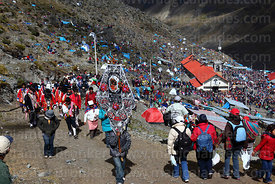 Man carrying banner ahead of dance group above Sanctuary, Qoyllur Riti festival