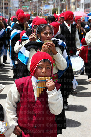 Young boy playing sicus or panpipes in sicuris dance group, Virgen de la Candelaria festival, Puno, Peru