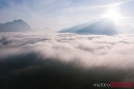 Aerial view of low clouds and mountain peak at sunrise