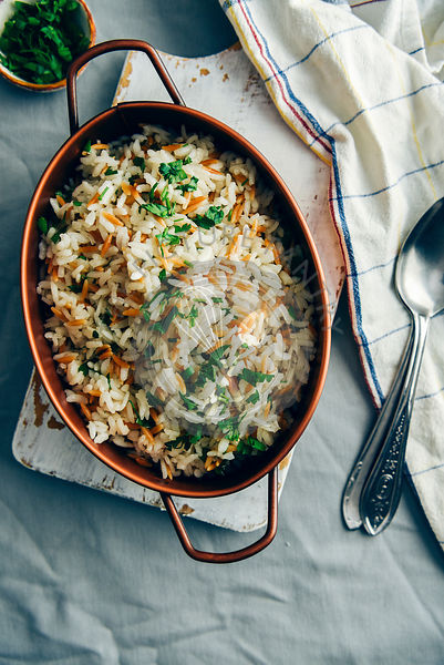 Fried rice pilaf with orzo served in a copper pan on a white board. Spoons, white napkin and a small bowl of chopped parsley accompany.