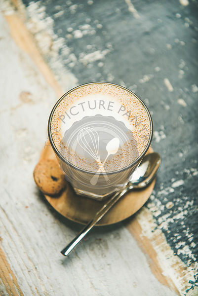 Cappuccino coffee in glass over wooden background