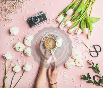 Female hands holding coffee, fresh flowers and film camera