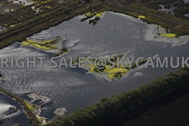 Chat Moss aerial photograph of Peat beds ponds created when the peat has been extracted leaving islands surrounded by bright green algae or pond weed possibly caused by fertiliser run off or other environmental factors.