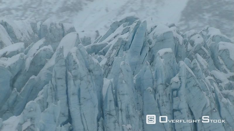 Flying over deep crevasses of glacier in Alaska
