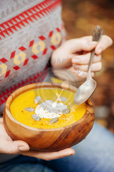 Woman holding pumpkin soup in a rustic bowl outside