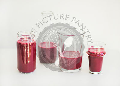 Fresh morning beetroot smoothie or juice in glasses, white background