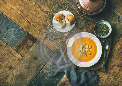 Flat-lay of fall warming pumpkin cream soup with croutons and seeds on board over rustic wooden background, copy space