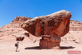 Man standing under big rock, Utah, USA