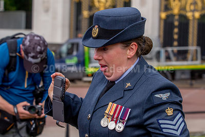 RAF airwoman looking socked as she is sprayed by The Royal Parks garden sprinklers.