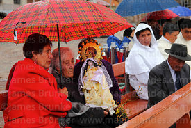 Devotees with Virgen de la Candelaria statue shelter from the rain before central mass, Puno, Peru