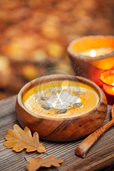 Pumpkin soup in a rustic bowl outside in autumn