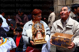 Woman leaving church holding ornate baby Jesus icon after mass for Reyes (Epiphany, January 6th), La Paz, Bolivia