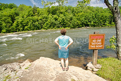 (MR) Female Visitor And Water Danger Sign Youghiogheny River At Ohiopyle, PA