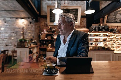 Senior businessman sitting in cafe, using digital tablet, daydreaming