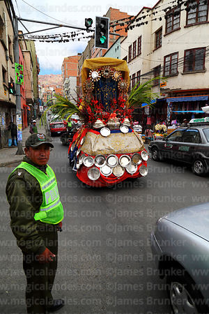 Decorated car driving past traffic policeman at crossroads on Good Friday, La Paz, Bolivia
