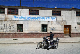Man riding motorbike past Association of Retired Railway Workers building, Uyuni, Bolivia