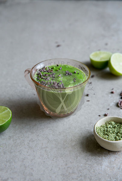 Healthy green vegetable and matcha smoothie drink with cocoa nibs
