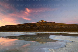 Tunupa volcano reflected in saline pool at sunset, Salar de Uyuni, Bolivia