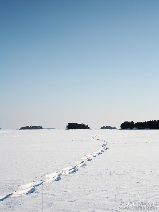 Tracks in frozen sea and islands landscape