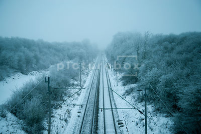 An atmospheric image of a frozon snow and Ice covered landscape with a train tracks going into the distance, in Northamptonshire, England.