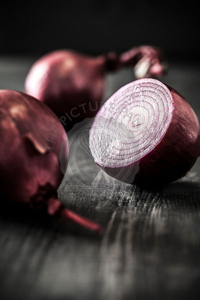 Red onion on black surface