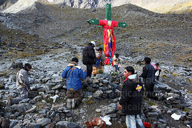 Believers praying at cross on the mountainside, Qoyllur Riti festival, Peru