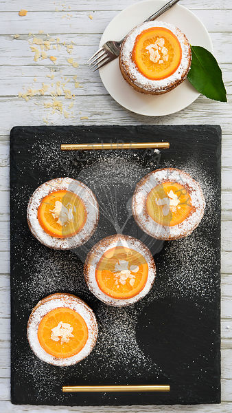 Small round orange cakes decorated with glazed orange slices, flaked almonds and powdered sugar and served on a black slate tray.