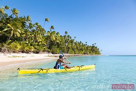 Man on kayak near beach in a tropical island, Fiji