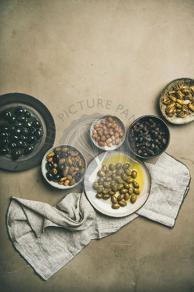 Various kinds of Mediterranean pickled olives in plates, copy space