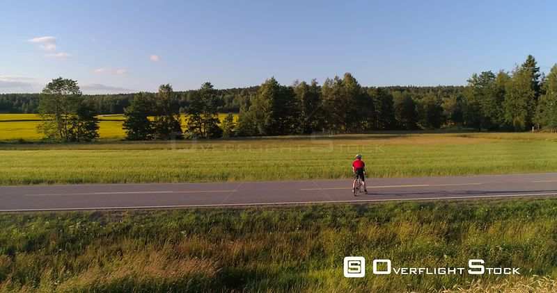 Man biking on the countryside, C4K aerial view around a biker driving on a road, between wheat fields, on a sunny summer evening sunset, in Uusimaa, Finland