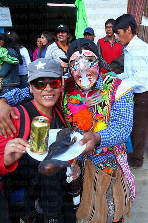 Masked Maqtas dancer serving llama foetus and beer at Virgen del Carmen festival , Paucartambo , Peru