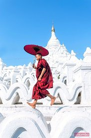 Young novice monk jumping on white pagoda, Myanmar