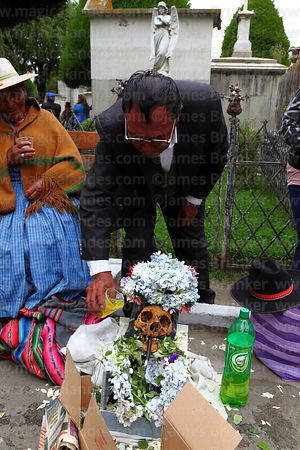 Man giving a cup of fizzy drink to a skull in cemetery, Ñatitas festival, La Paz, Bolivia