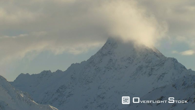 Flying past cloud-capped jagged peak in Alaska
