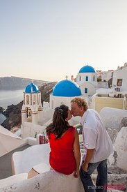 Adult couple kissing, with blue domed village of Oia in the background