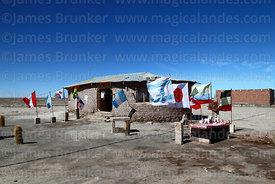International flags and souvenir stall outside salt house, Colchani, near Uyuni, Bolivia