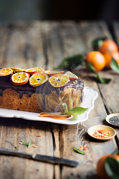 Tangerine loaf cake with chocolate glaze on rustic wooden table