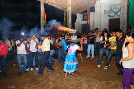 Woman with fireworks exploding on his hat runs into crowd in front of church, San Ignacio de Moxos, Bolivia