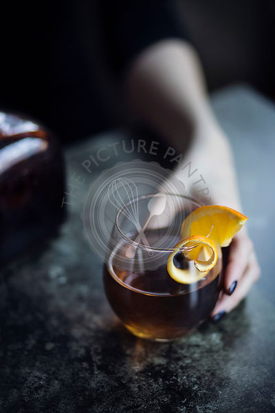 Hand of woman sitting at bar holding a alcoholic drink