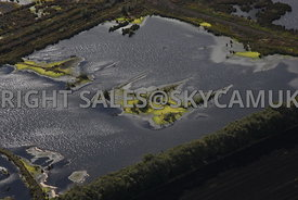Chat Moss aerial photograph of the Peat beds and the ponds created when peat has been extracted leaving islands surrounded by bright green algae or pond weed.