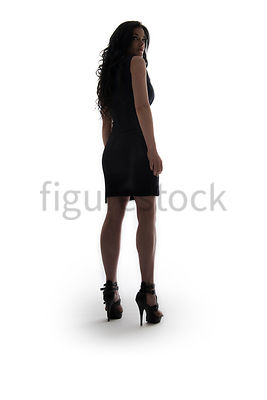 A Figurestock image of a woman, standing and looking over her shoulder – shot from low level.