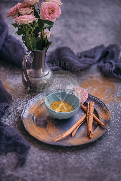 Turmeric powder in a small blue bowl and cinnamon sticks on a grey plate